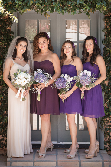 bride with her bridesmaids all holding white and purple bouquets