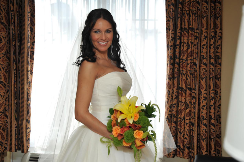 bride by the window with orange and yellow bouquet