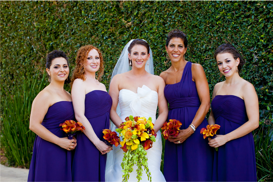 bride with bridesmaids in front of hedge wall